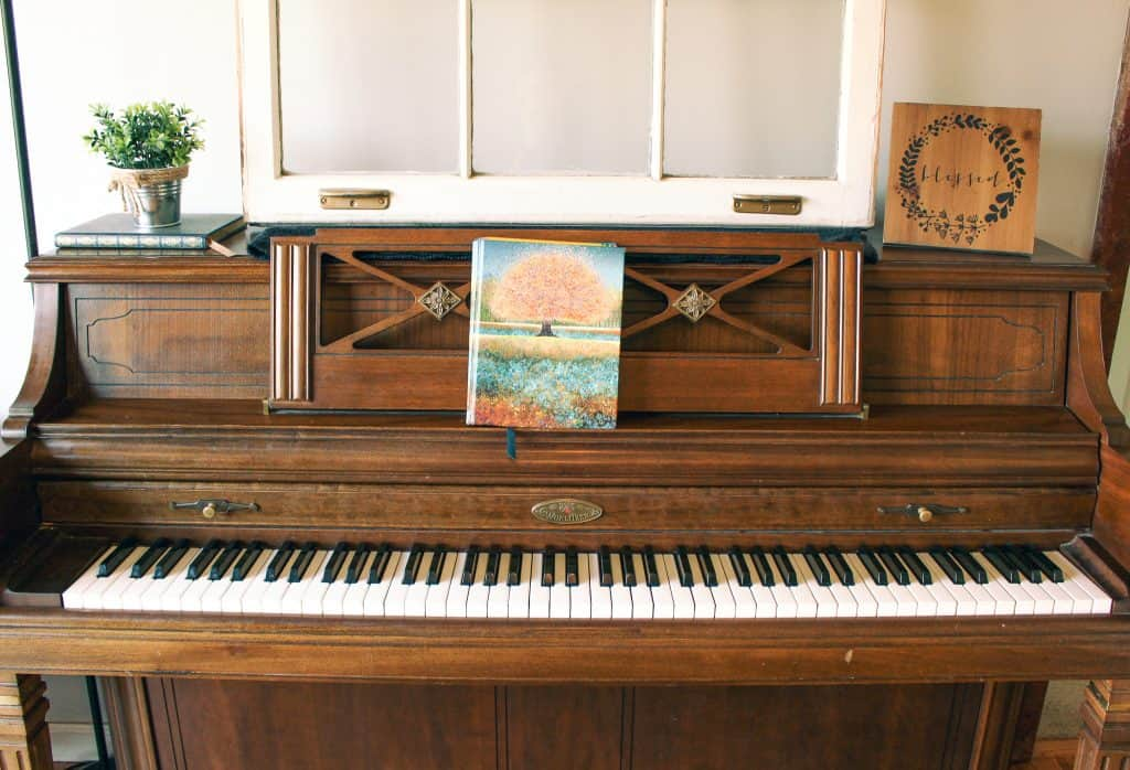 decorated wood piano with songwriting journal