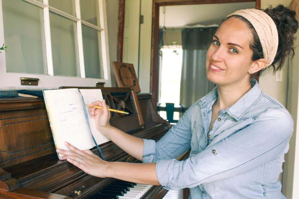 woman smiling and songwriting at an old piano