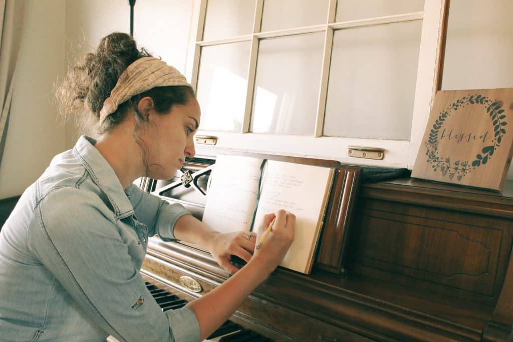 inspired looking woman writing songs at old piano