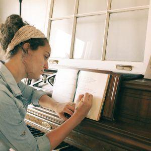 woman songwriting at old piano