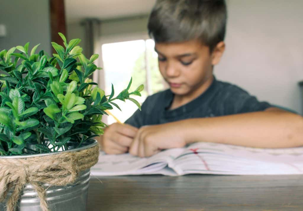 boy writing in math book at dining room table