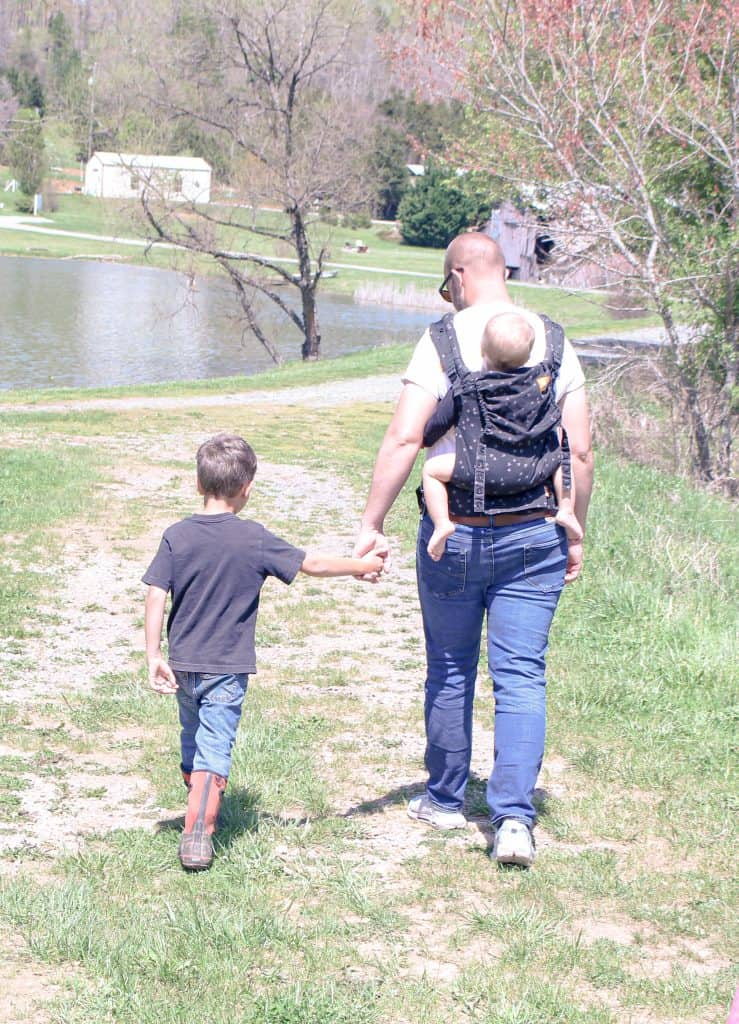 father carrying baby on his back and holding the hand of young son next to a lake