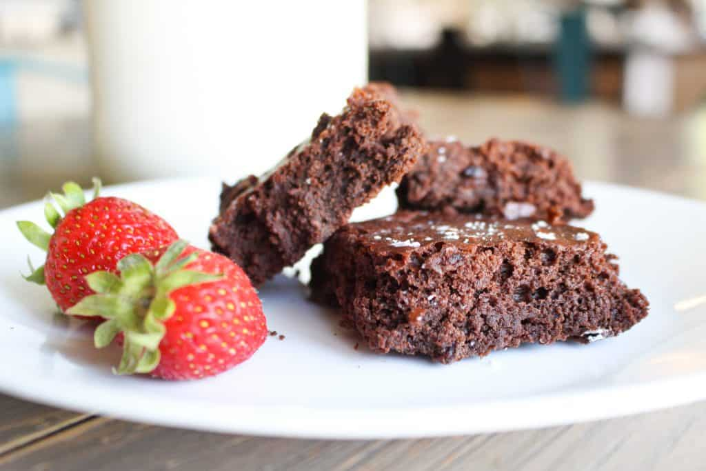 cut sourdough brownies on plate with strawberries