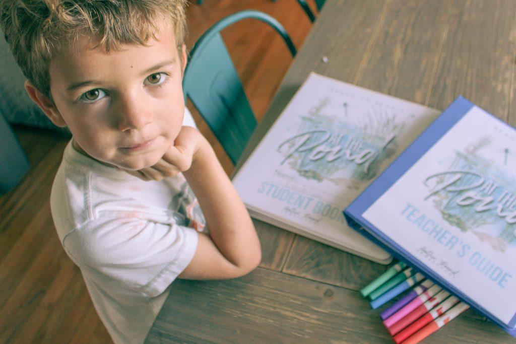 kindergartener with homeschool curriculum and markers