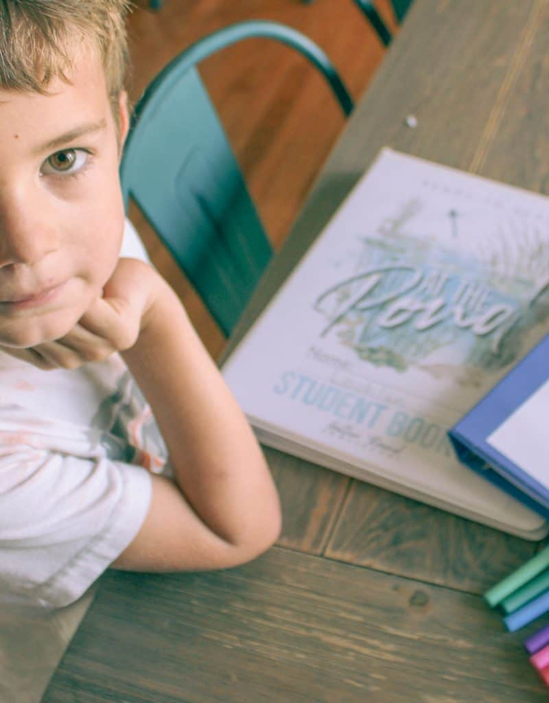 kindergartener at table with homeschool curriculum and markers