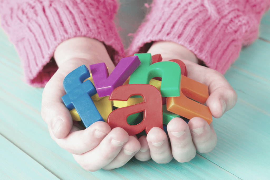 letter magnets in child's hands